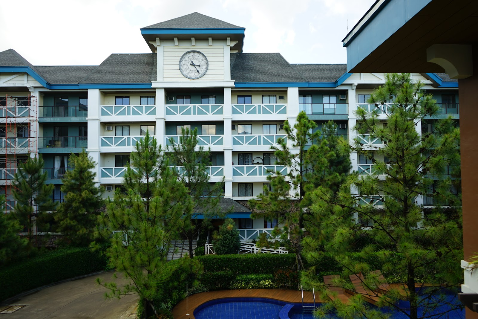 Pine Suites condo development in Tagaytay surrounded by pine trees and vibrant greenery with Danish blue modern condo architecture