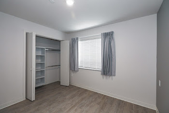 Apartment Bedroom with window, closet, and shelving organizer in closet