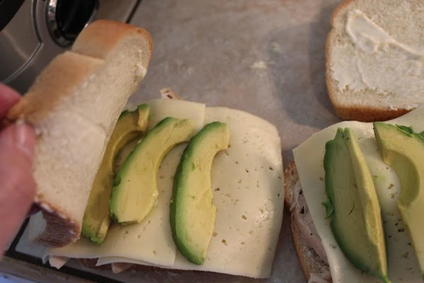 Place chicken meat, cheese slices, and avocado on one side of bread, then top...