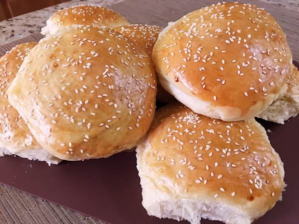 Hamburger Buns With Sesame Seeds On A Cutting Board.