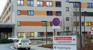 Klinikgebäude, Haupteingang mit Taxi.