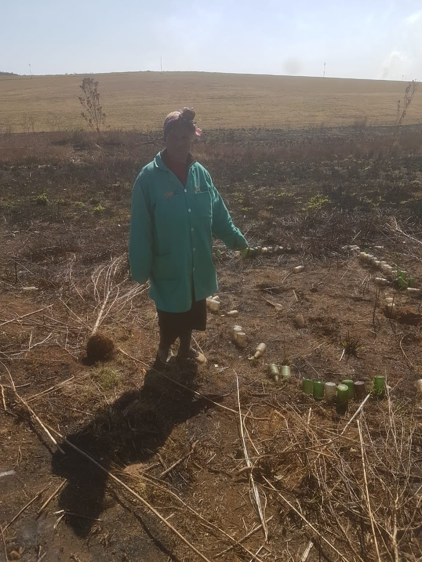Community representative Fikile Maharaj pointing one of the still visible graves after their ancestral graves were demolished by the farmer.