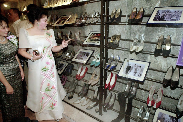 This file photo taken on February 16 2001 shows Philippines's former first lady Imelda Marcos accompanied by tourism official Marides Fernando as she looks at her shoe collection, after formally opening the suburban Marikina Shoe Museum in Manila. Picture: AFP/JOEL NITO
