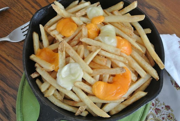 Divide the french fries into 2 - 8 ounce cast iron skillets for individual...
