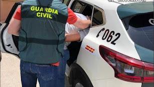Imagen de un Guardia Civil con un detenido.