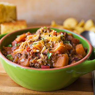 """Cheesy Sweet Potato """"Skillet Chili"""" with Lean Ground Beef, Red Bell Peppers, Tomatoes and Red Beans, with Sharp Cheddar and Green Onions."""