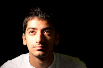 Photo: Requirement 1:  Our friend here was the perfect model with excellent color in his eyes to boot. Here, we tried to get the 'Rembrandt triangle' on the left side of his face. As the background was the black curtains, the photo was underexposed by 1 stop. The main lighting came from the key-light lamp to the left side of thephoto. In addition, a stronger fill lamp was used above and to his side to create the 'triangle'.  The nifty50 really was an excellent portrait lens on a crop body, and wide aperture (perhaps too wide!) was used to isolate the subject.
