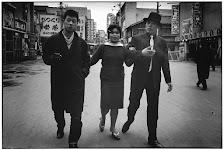 2 mannen en een vrouw wandelend op straat