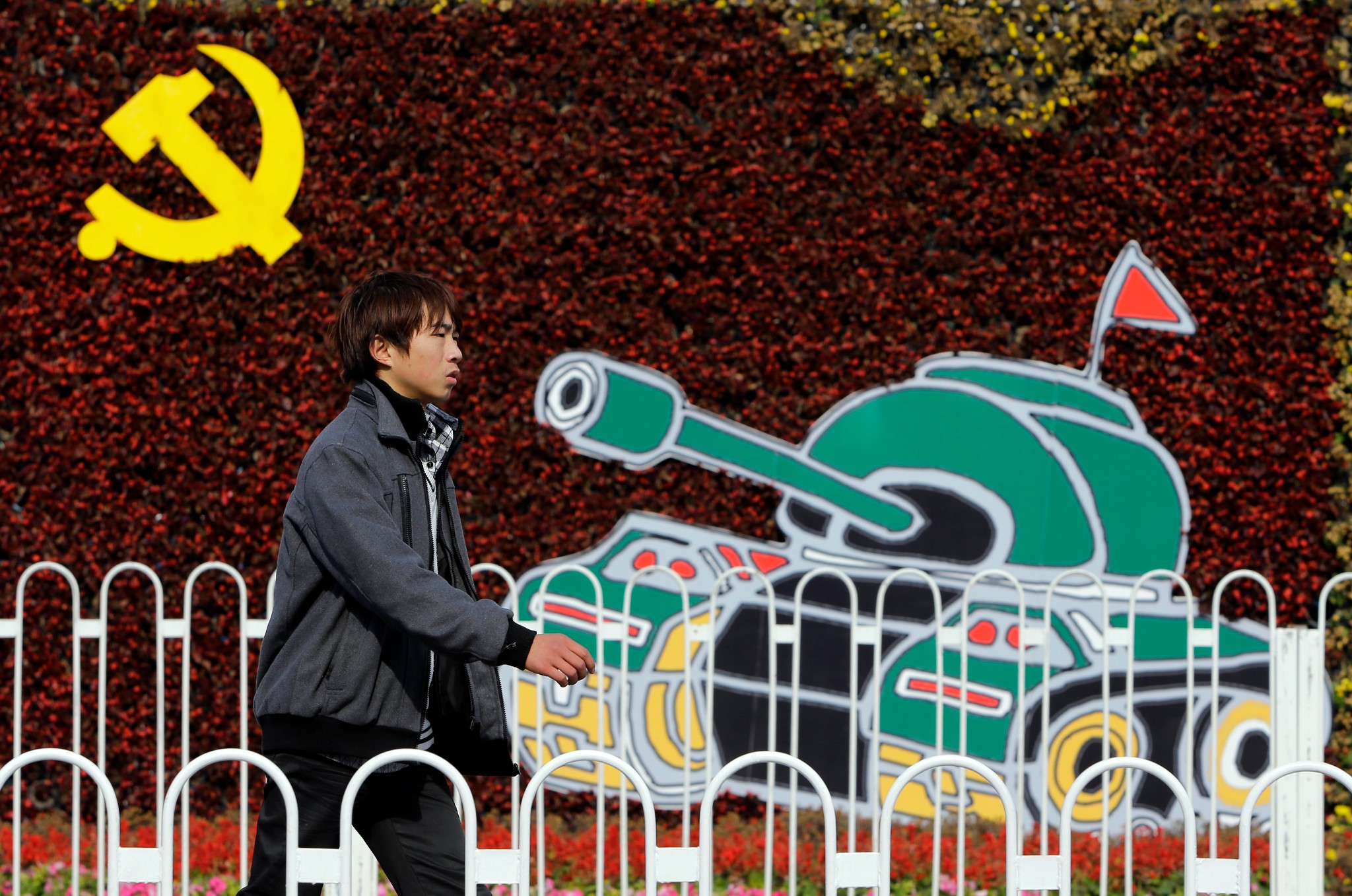 Photo: A man walks past a decoration wall outside the Chinese Military Museum celebrating the congress.