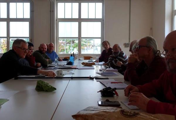 Sitzend am Tisch mit Papieren, die Teilnehmer:innen.