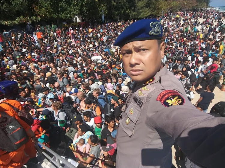 Lombok Water Police Chief Dewa Wijaya takes a picture in front of hundreds of people attempting to leave the Gili Islands after an earthquake Gili Trawangan, in Lombok, Indonesia, on August 6, 2018, in this picture obtained from social media. Picture: INDONESIA WATER POLICE/VIA REUTERS