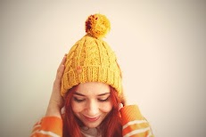 A girl wearing Mustard colored woolen beanie with a pom pom.