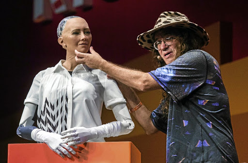 BACK TO THE FUTURE: Ben Goertzel, chief scientist at the Hong Kong-based Hanson Robotic describes to the audience what 'Sophia the Robot' is made of during a discussion about the future of humanity in a demonstration of artificial intelligence at the RISE Technology Conference at the Hong Kong international convention centre on Wednesday. Artificial intelligence is the dominant theme at this year's conference but the live robot exchange took the AI debate to another level Picture: ISAAC LAWRENCE/AFP PHOTO