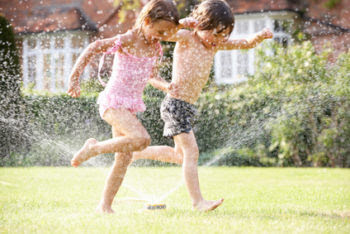 two kids running through sprinkler