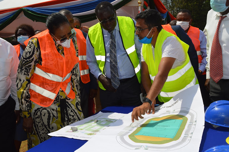 From left) sports cabinet secretary Amina Mohammed with Governor James Nyoro being shown the Kirigiti stadium in Kiambu town plans by the contractor