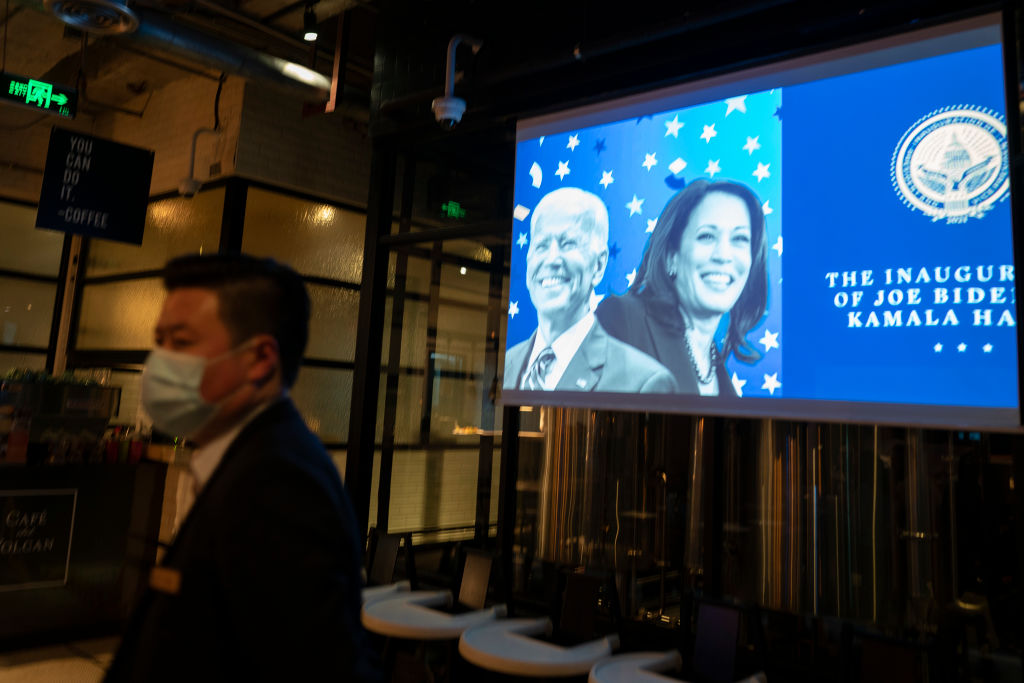 A projector shows the inauguration of Joe Biden as 46th President of the United States as seen at a bar on January 21, 2021 in Shanghai, China. Biden's modification of Trump's November of 2020 Order on Chinese Military companies has been revised to remove 16 companies, move placement power from the Defense Department to Treasury, and neutered all wording involving the CCP or communism.