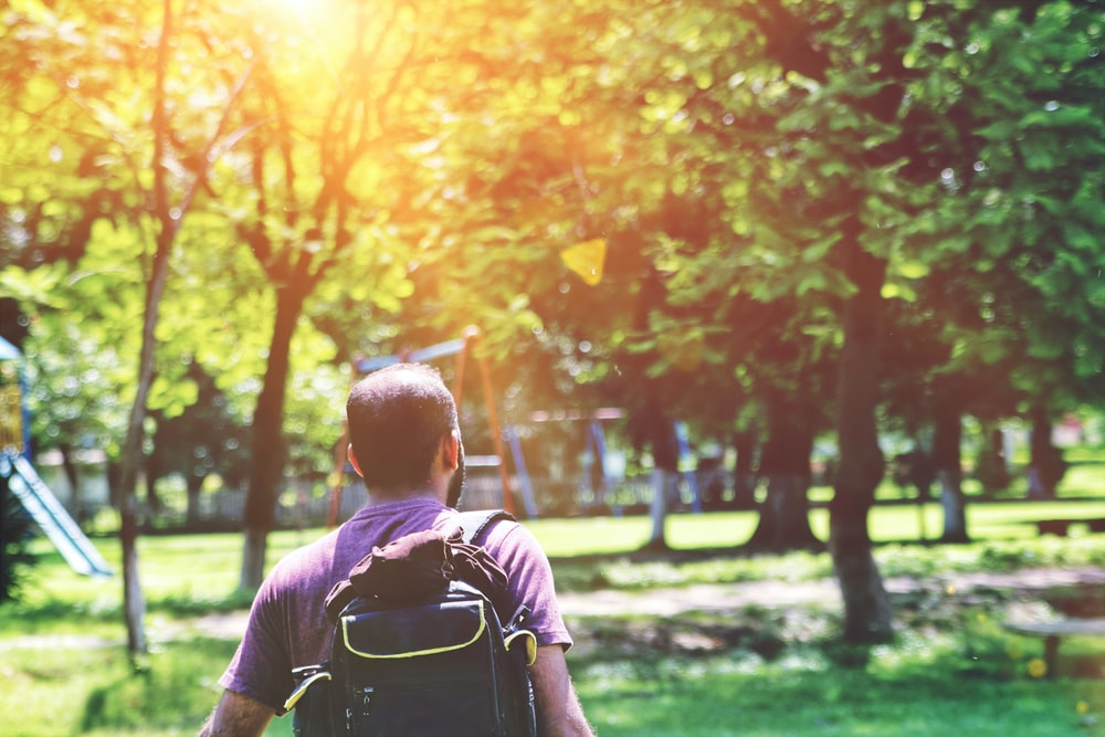 man in black t-shirt with black backpack walking near trees
