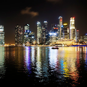 by Jenny Zhang - City,  Street & Park  Night ( illuminated, famous, skyline, reflection, metropolis, exterior, travel, cityscape, architecture, singapore, business, city, modern, center, sky, skyscraper, southeast, asia, marina, district, commercial )