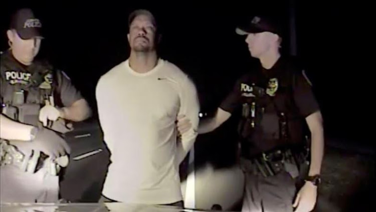 Tiger Woods is seen handcuffed and searched by police officers in this still image from police dashcam video in Jupiter, Florida, U.S. on May 29, 2017. Courtesy Jupiter Police Department/Handout via REUTERS
