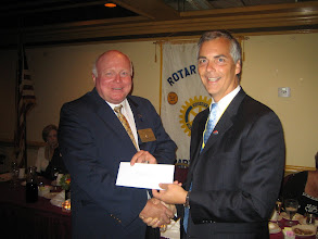 Photo: President Joe presenting District Governor Bill Griffin with the club's check to the PolioPlus Program
