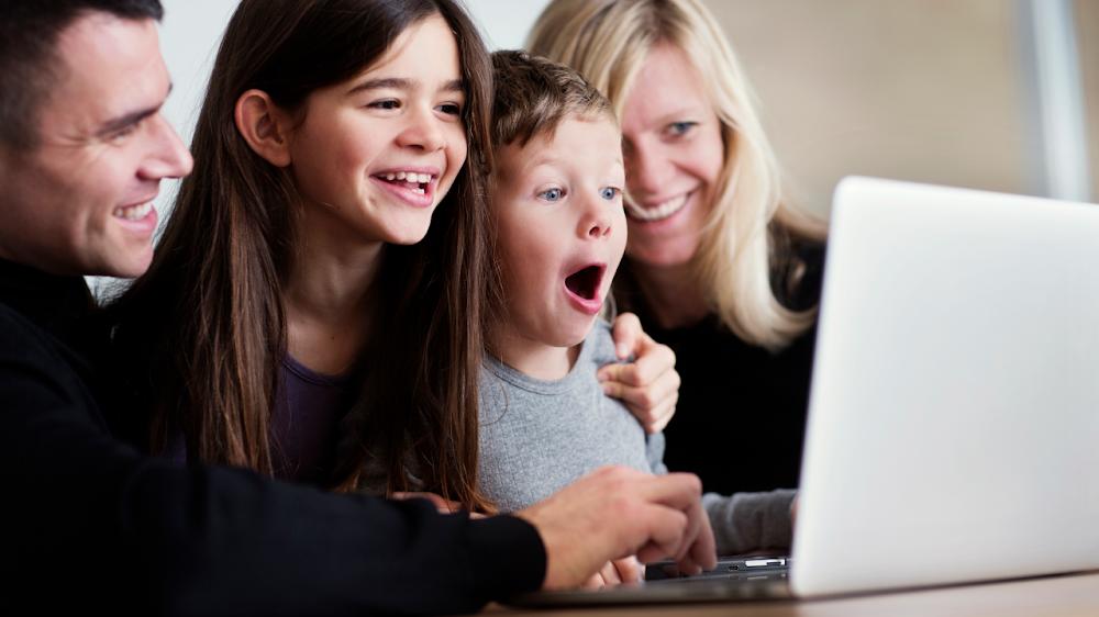 Una familia mirando un ordenador con caras de felicidad y sorpresa