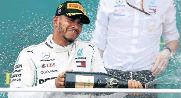 Race winner Lewis Hamilton, of Great Britain and Mercedes GP, celebrates on the podium during the Azerbaijan Formula One Grand Prix at the Baku City Circuit yesterday