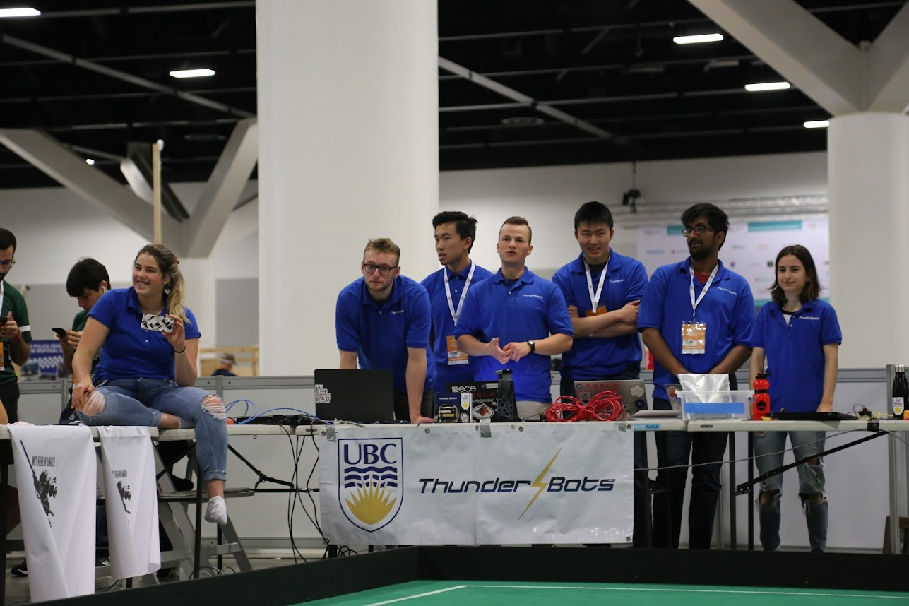 Group of students who compete in robotics standing by table