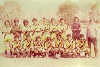 Photo: 16-4-1975 ΑΕΚ Κυπελλούχος ΕΠΣ ΒΔΜ 1974-75 Ορθιοι: Γιάννης Μάστορας, Κώστας Μούρτζιος, Πασχάλης Πουρνάρας, Τάκης Πλιάκης, Τάκης Πάσιος, Τάκης Κοζιάκης, Γιώργος Κουζιάκης, Χάρης Ζέρβας, Γιώργος Τιάλιος (προπονητής). Καθιστοί: Πάσχος Βαλαής, Τάκης Δαϊρούσης, Ηλίας Πιτσιάβας, Βασίλης Κουζιάκης, Τάσος Χατζηγιετήμ, Αγγελος Γούσιας, Ακης Μπαρτζώκας.