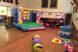 a Play Area in a School Hall with soft play toys and a jumping castle
