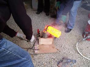 Photo: Coulée du laiton. Les fumes blanches sont trés dangeureuses: vapeurs de zinc. Opérer dehors ou en abri ventilée.