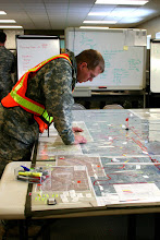 Photo: Staff Sgt. Matthew Hurt, a 2nd Combined Arms Battalion, 136th Infantry Regiment Soldier looks over a map before a mission during Flood Fight 2009 at the Moorhead Armory on March 28.