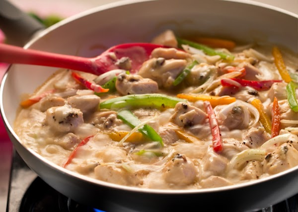 Melt butter in a large frying pan.Saute chicken, onion and bell pepper until chicken...