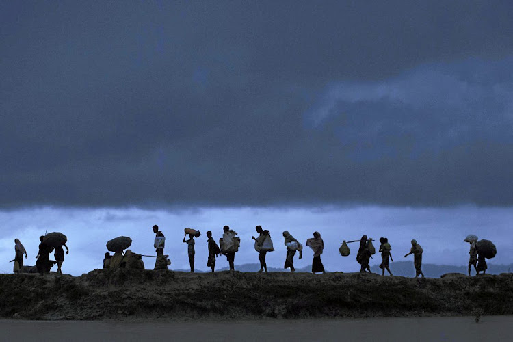 Rohingya refugees walk over paddy fields at dusk after crossing the border from Myanmar. File photo.