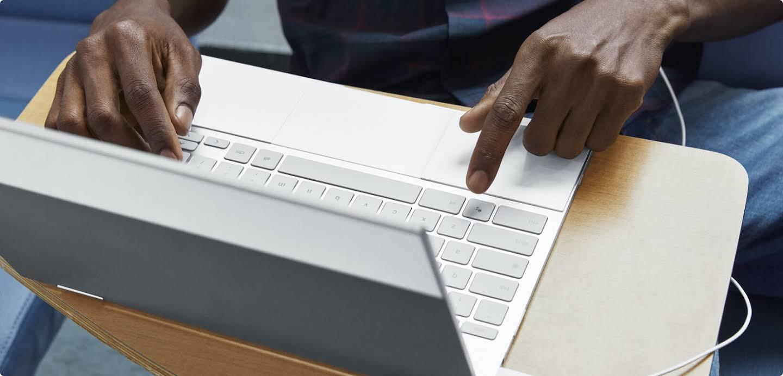 在筆記型電腦鍵盤上打字的手。