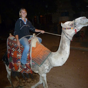 Woman Camel Riding in Cairo Egypt alongside the Giza Pyramids at Night
