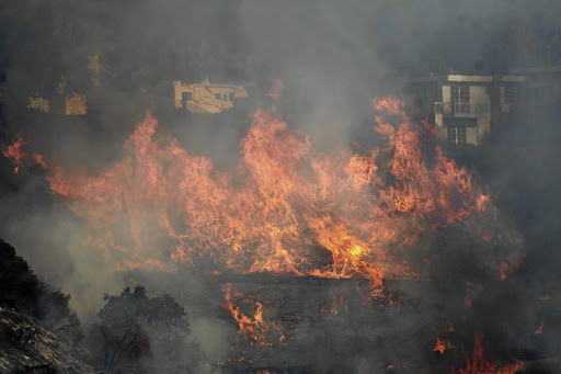 Fires rage on a hillside in a wealthy neighbourhood on the west side of Los Angeles, California. Picture: REUTERS