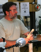 Photo: Not all of his tools are purchased. Here he shows a band saw blade he uses to part with. He uses it to mark where the bottom of the bowl will be.