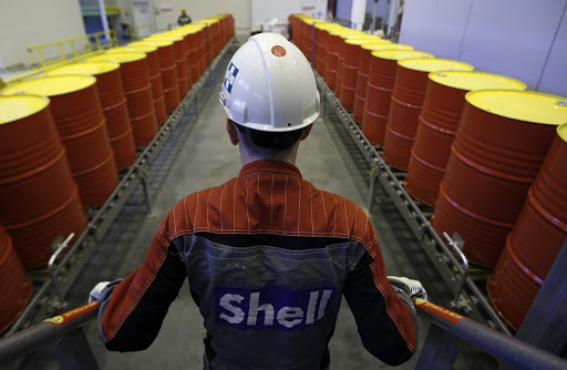 LINED UP: An employee stands in front of oil barrels at Royal Dutch Shell's lubricants-blending plant in the town of Torzhok, Russia. Picture: REUTERS