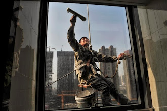 Photo: A labourer cleans the window of an office building near a residential complex (back) under construction in Shenyang, Liaoning province in this May 17, 2013 file photo. China's factory activity shrank for the first time in seven months in May and growth in the services sector cooled, evidence that the world's second-largest economy is losing further momentum in the second quarter. The HSBC/Markit Purchasing Managers' Index (PMI) for May dropped to 49.2, the lowest level since October 2012 and down from 50.4 in April, as domestic and overseas demand fell.   REUTERS/Stringer/Files (CHINA - Tags: BUSINESS CONSTRUCTION POLITICS)