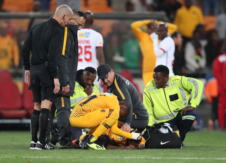 Khama Billiat comforts teammate Joseph Molangoane (lying on floor) after the former sustained a horrific injury during the MTN8 quarterfinal match against Free State Stars at FNB Stadium on Saturday August 11 2018.