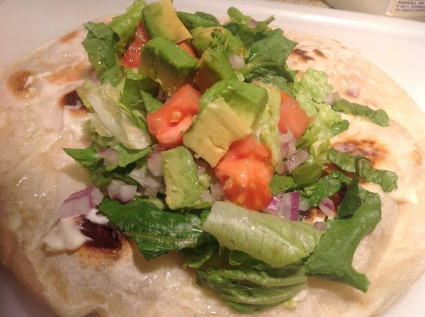 To tortilla, add a handful of shredded lettuce, chopped red onions, chopped tomatoes and...