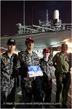 Photo: The crew of HMAS Sydney wear Swannies' hats and have a mounted laminate of the match day banner between the Vietnam Swans and HMAS Sydney. Deck of HMAS Sydney, Saigon Port, 2 November 2012.