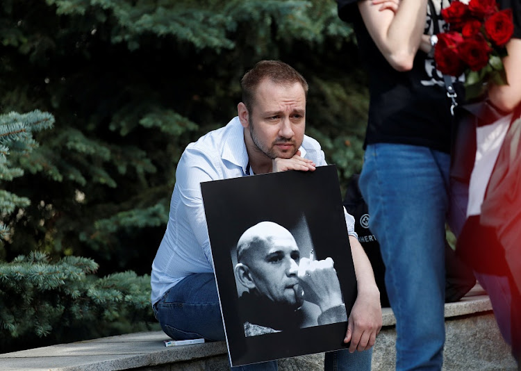 A man holds a portrait of Alexander Rastorguyev, one of three Russian TV journalists killed in volatile Central African Republic, during his funeral ceremony in Moscow, Russia August 7 2018. Picture: REUTERS/Maxim Shemetov