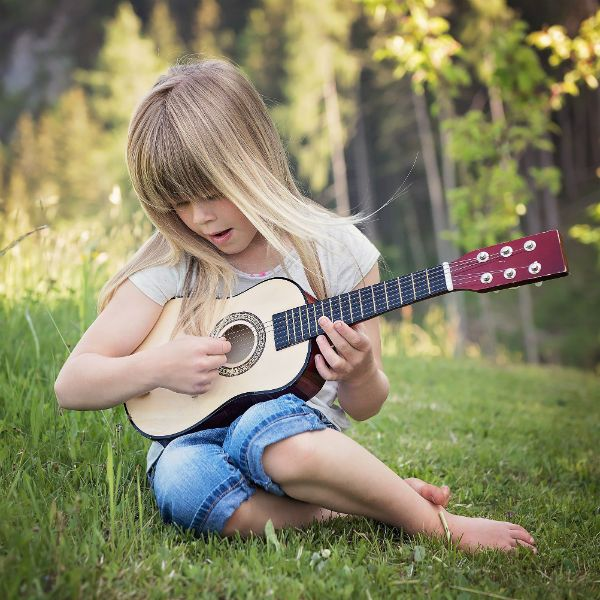 Niña tocando una guitarra con cuerdas de acero sentada en la grama
