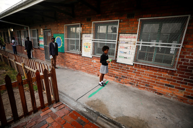 Learners observe social distancing markers as they queue at a school feeding scheme in Gugulethu,Cape Town. Picture: REUTERS/Mike Hutchings
