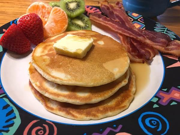 A Pile Of Pancakes Served On A Plate With Butter, Maple Syrup, A Few Strips Of Bacon, Strawberries, Oranges And Kiwifruits.