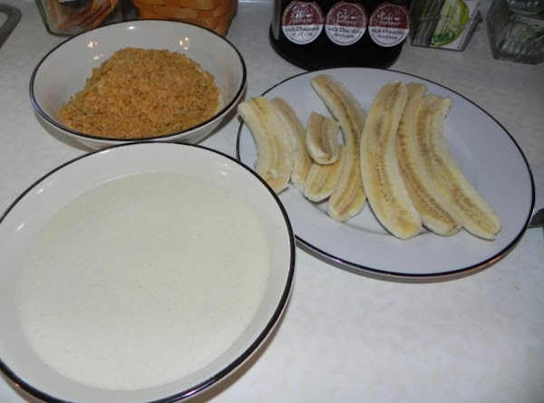 Dip bananas into milk mixture; roll in cornflakes and set aside.