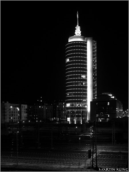Photo: Central Tower - Munich  I know it's not #monochromemonday anymore but although I fully intended to catch the brilliant blues this tower shows at night I surprisedly ended up monochrome during post processing. And who am I to dispute the judgement of the two great Ladies +Elizabeth Lundand +Mary Sassy Clarkso here I present you the bw version. Actually this is a stitched job with four vertical shots I took around midnight across the railroad lines leading to Munich main station.  As this was on the way back from a photowalk I tag +Muenchner Fotografenas well ... :-)