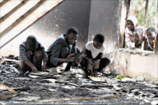 DASHED HOPES: These youngsters play inside the burnt down public library at Siyathemba in Balfour, Mpumalanga. The building and the books were destroyed by angry residents. PIC: BAFANA MAHLANGU  18/02/2010. © Sowetan.