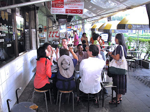 """Photo: Kasma counts hands for noodle breakfast choices at """"Saew,"""" a popular Thonglor noodle shop with tables on the sidewalk."""